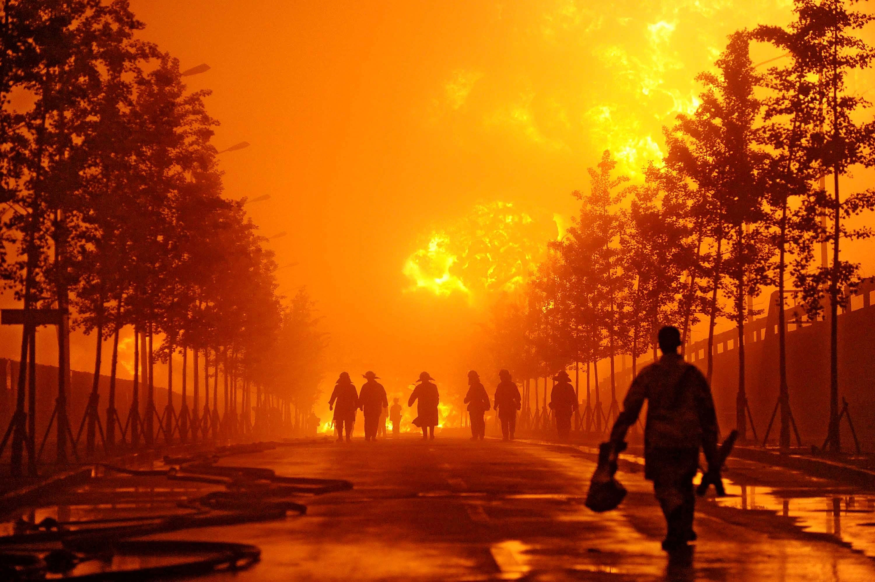 Fire fighters walk near flames towering from a pipeline explosion at a Chinese port in Dalian in northern China's Liaoning province yesterday.