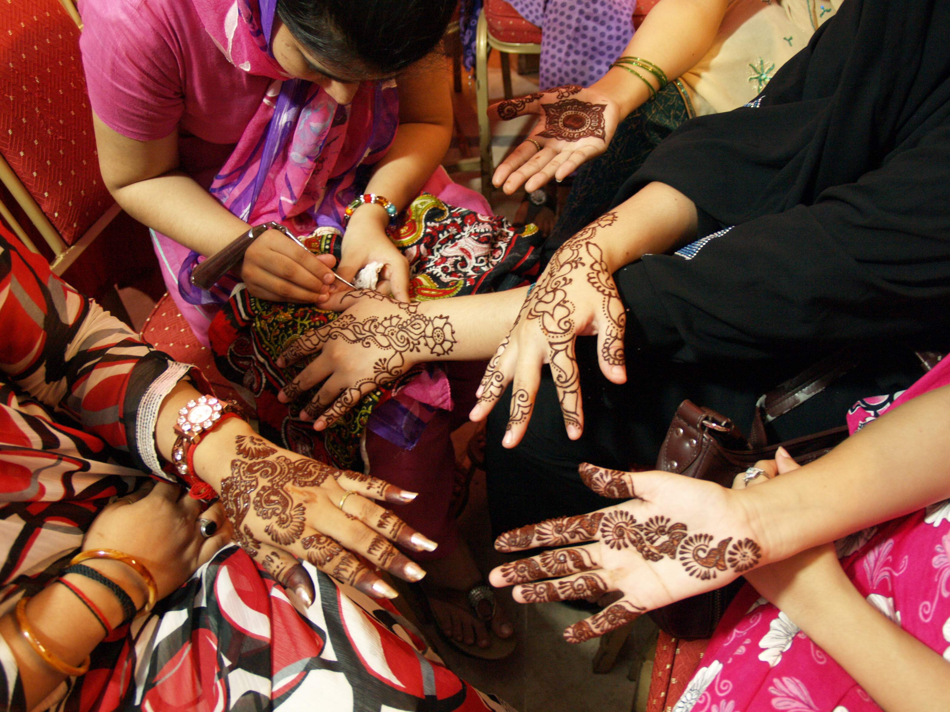 A Pakistani girls paints hands of her friend with henna to celebrate the Eid, ending of fasting month of Ramadan in Hyderabad, Pakistan on Friday.