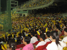 Cheerleaders and baseball fans, some wearing in Brother Elephants' iconic yellow jerseys, clapping rhythmically and cheering for their favorite team a...