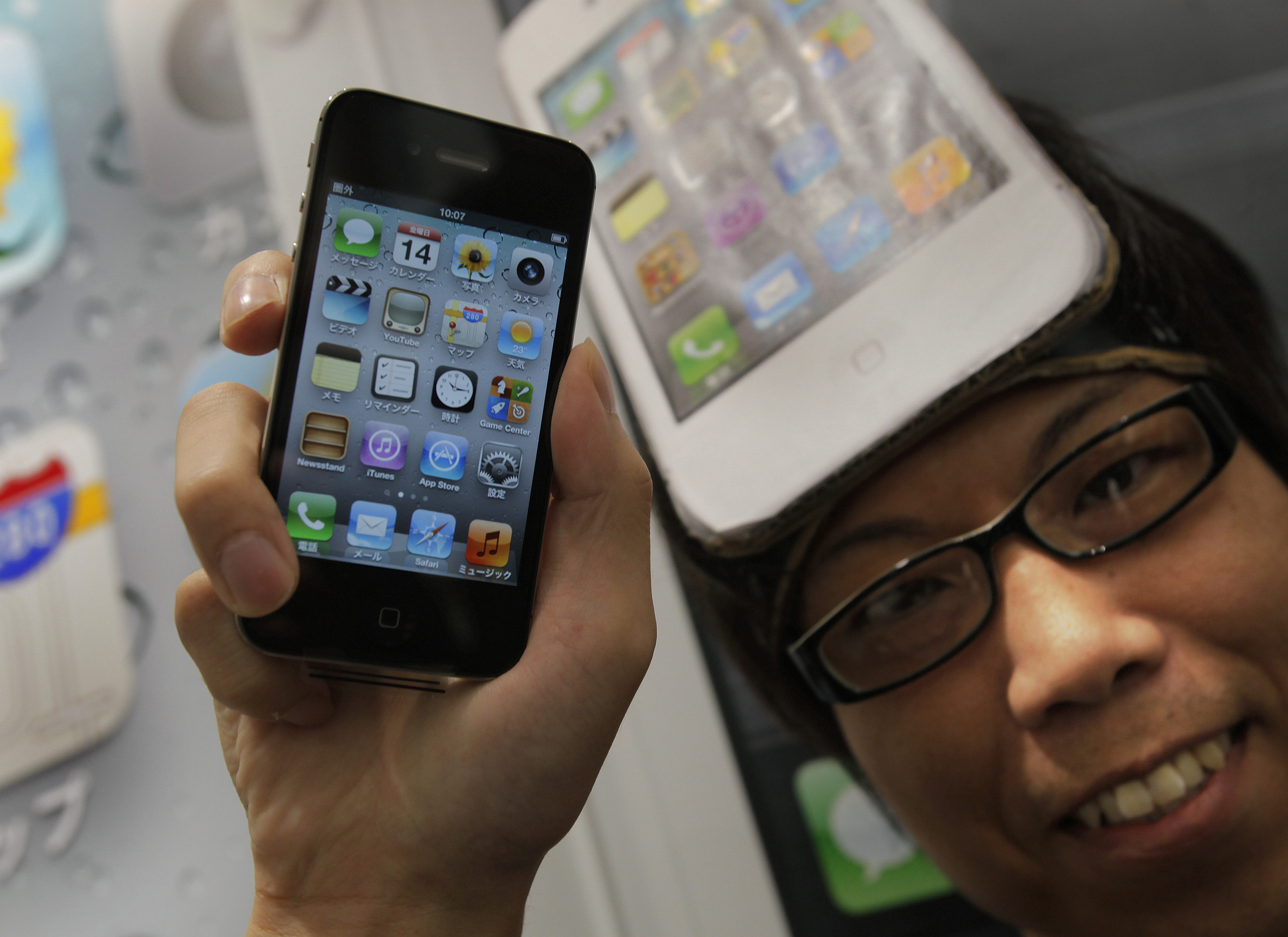 A customer shows his iPhone 4S after getting the latest smartphone at a Softbank Mobile Co. shop in Tokyo on the launch day in Japan Friday, Oct. 14,