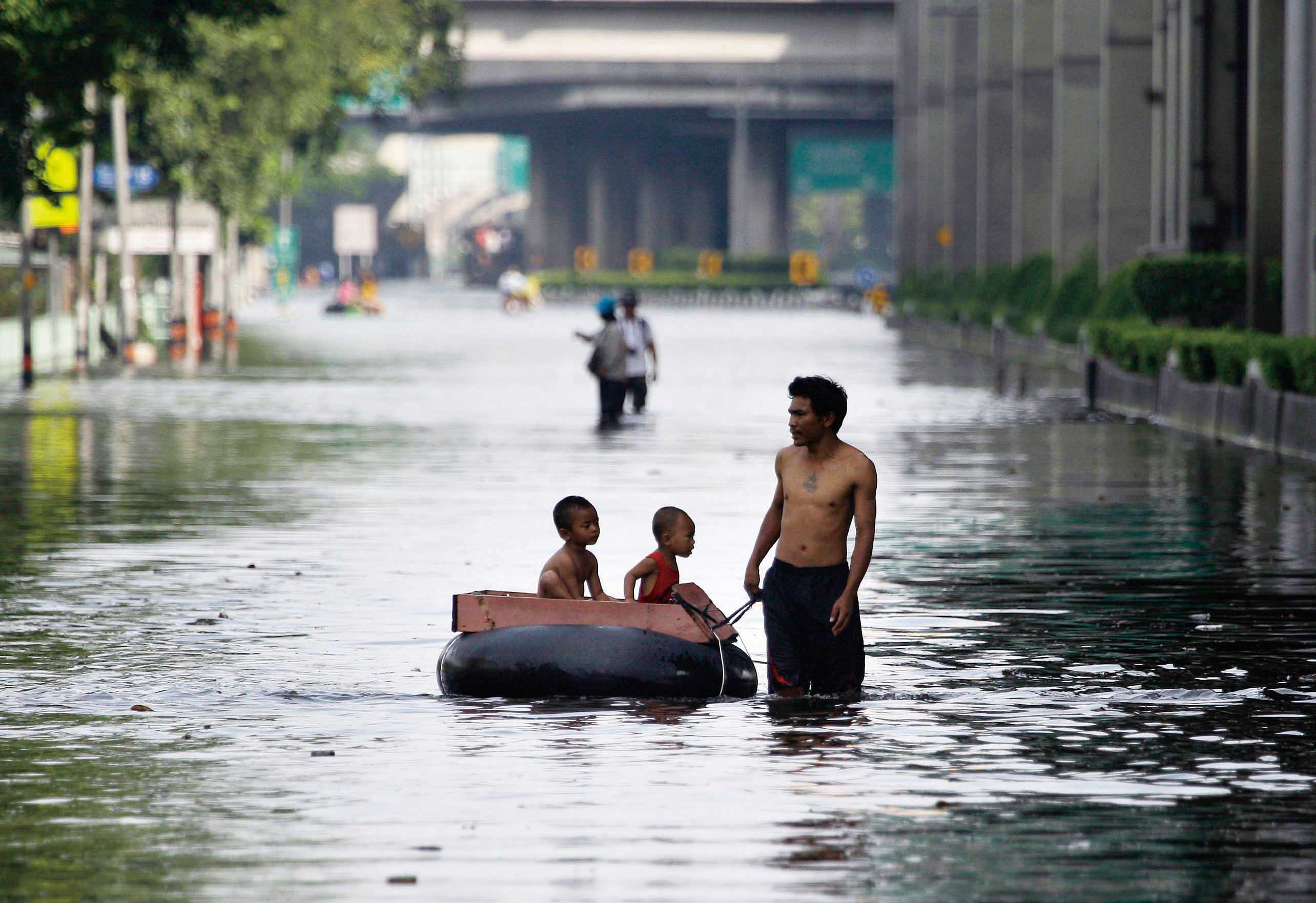 A Thai man pulls an improvised float to ferry children along flooded streets at the Lad Phrao district in Bangkok, Thailand, Saturday, Nov. 5, 2011. (...