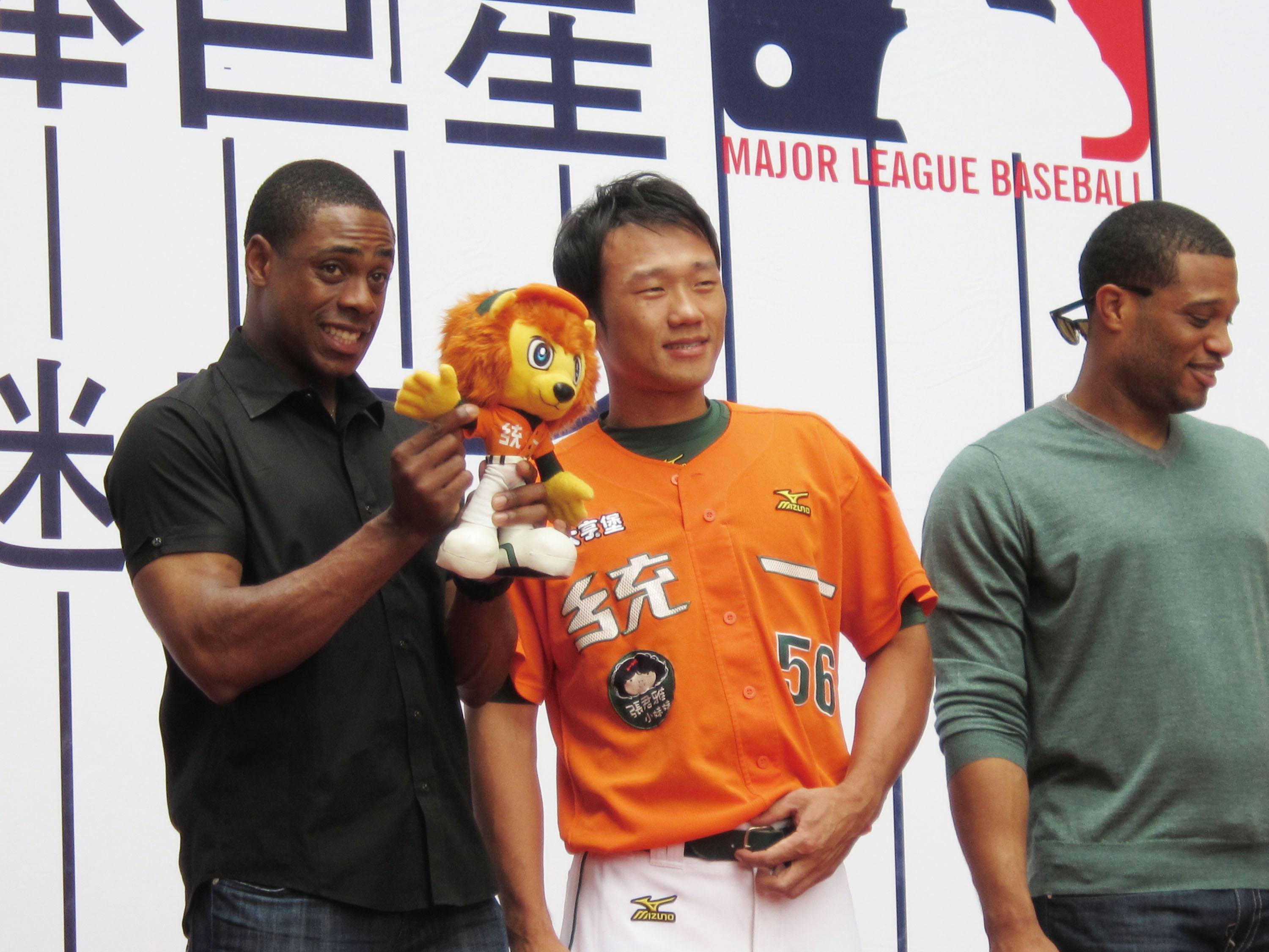 New York Yankees player Curtis Granderson (left) attends a fans party and takes a photo with Taiwanese UniPresident Lions Baseball Team player Liu Fuh...
