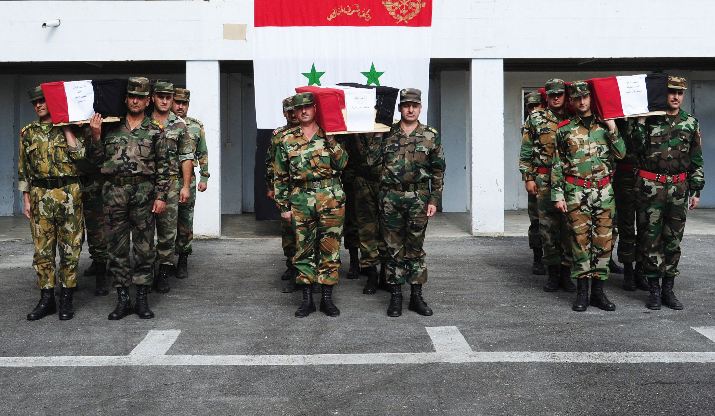 A photo released Syria's official news agency (SANA) shows Syrian soldiers carrying the coffins of comrades reportedly killed in recent fighting in th...