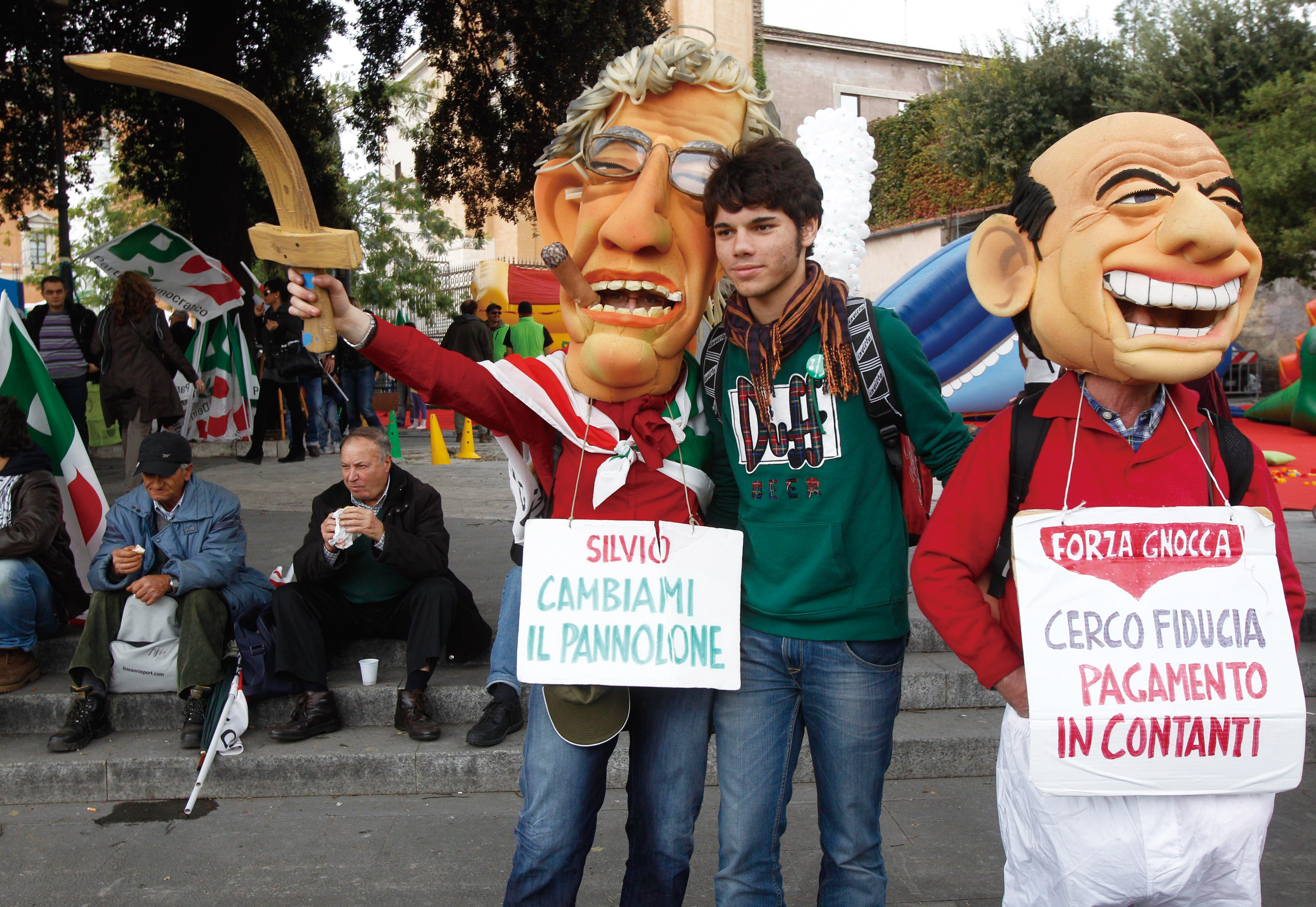 "Demonstrators wear masks mocking Italian Premier Silvio Berlusconi, right, and Reform Minister Umberto Bossi carrying placards reading: ""Silvio, chang..."