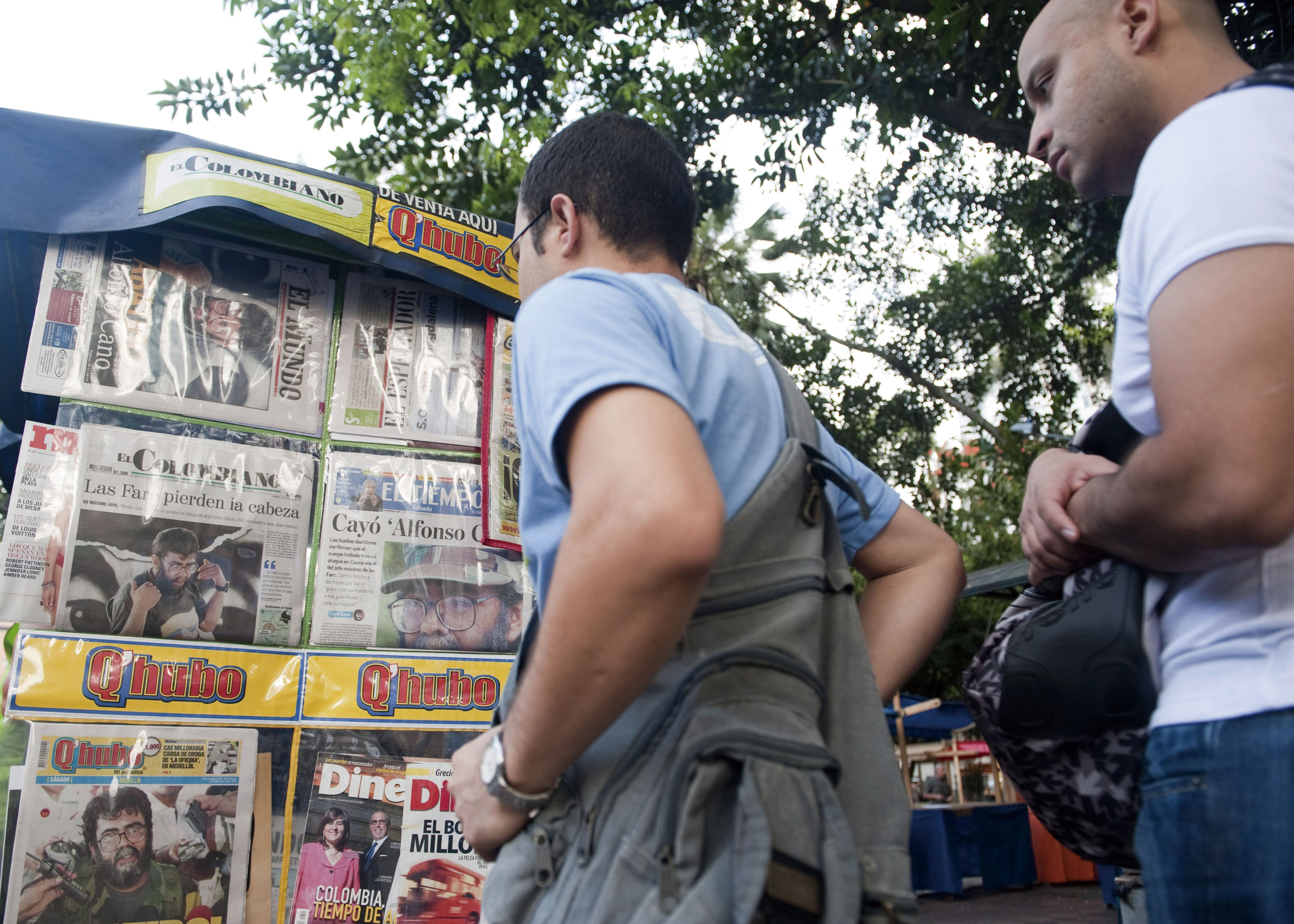 Passers-by look at newspapers reporting on the death of the leader of the Revolutionary Armed Forces of Colombia (FARC), Alfonso Cano, at a newsstand ...