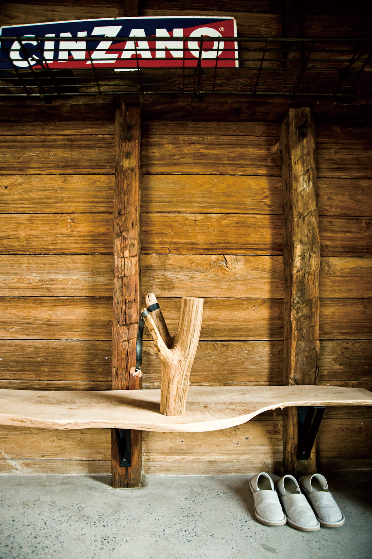 A bench, made from a slab of oak and attached to the wall with brackets custom-made by a local blacksmith, inside the entrance of the barn on Fabio Ch...