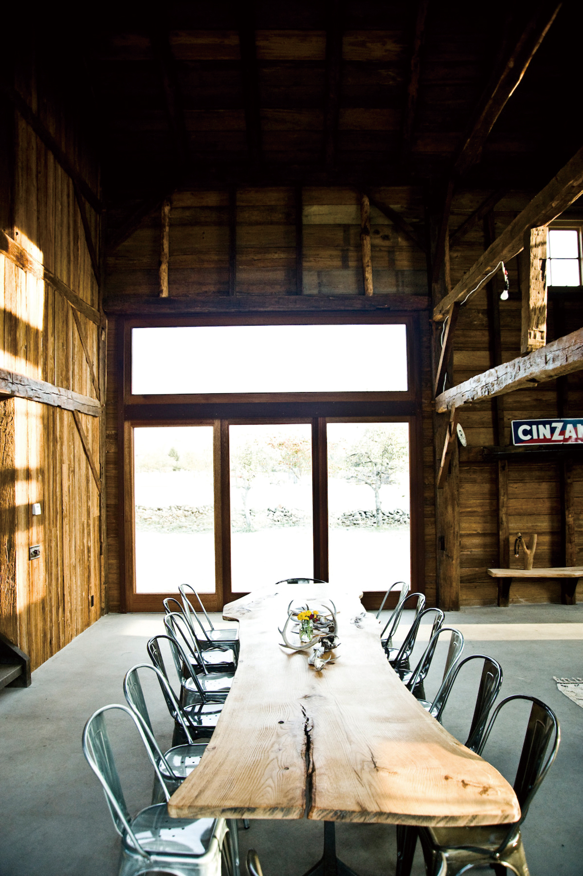 A dining table, which was custom-made from a slab of oak, furnishes the barn on Fabio Chizzola's 32-acre apple orchard, in Accord, N.Y., Oct. 31, 2011...