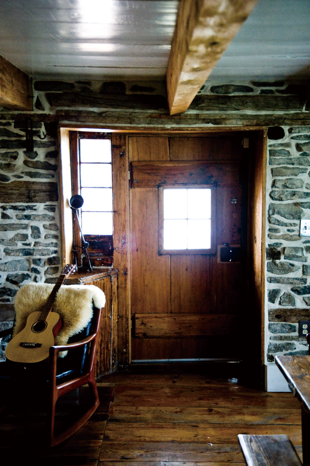 The front door, which is rarely used, inside the old stone farmhouse of Fabio Chizzola, furnished with a mid-century rocking chair from Spruce, on Chi...