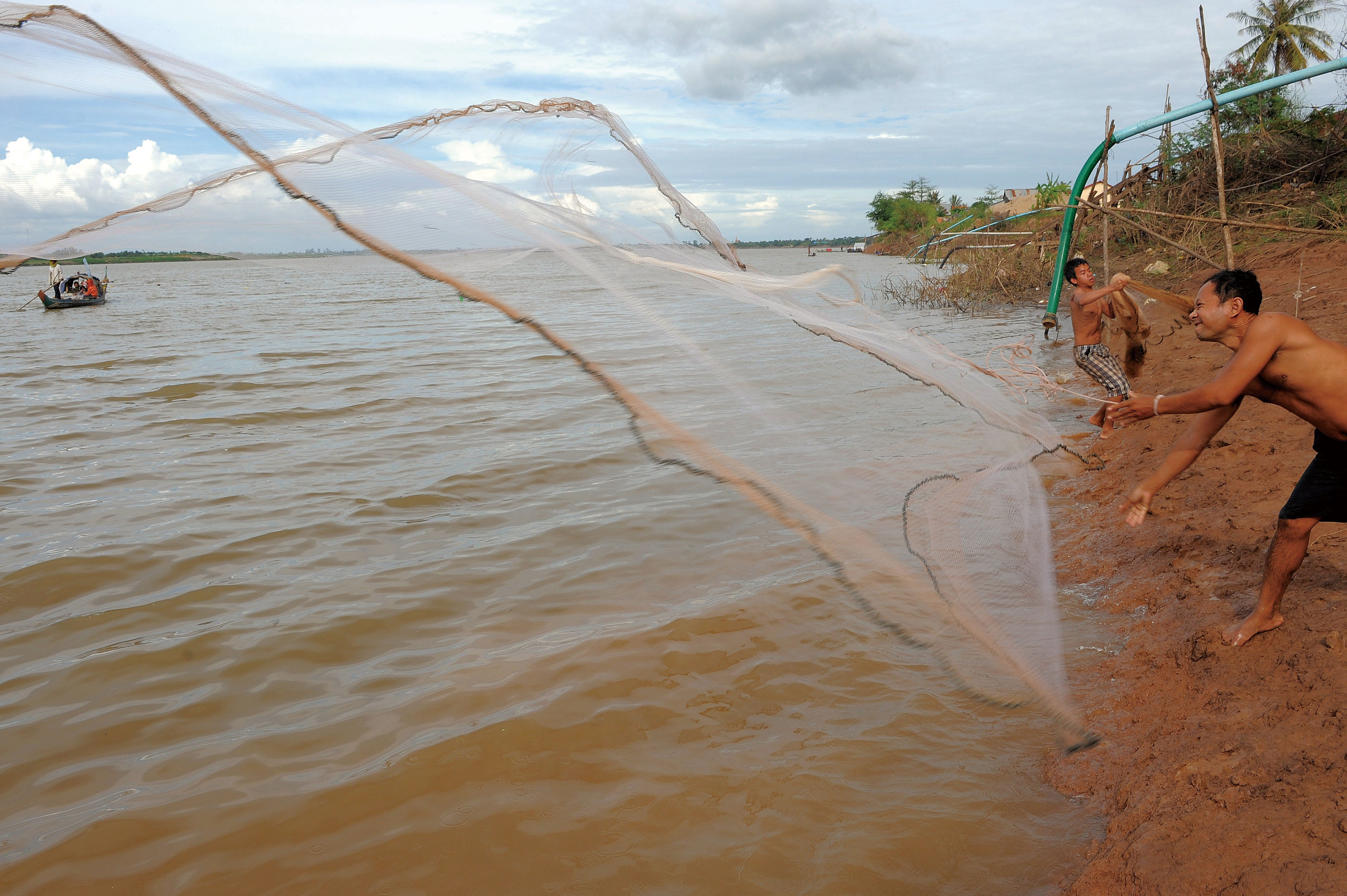A Cambodian man throws his net into the Mekong river on the outskirts of Phnom Penh on December 8, 2011. (Agence France-Presse)