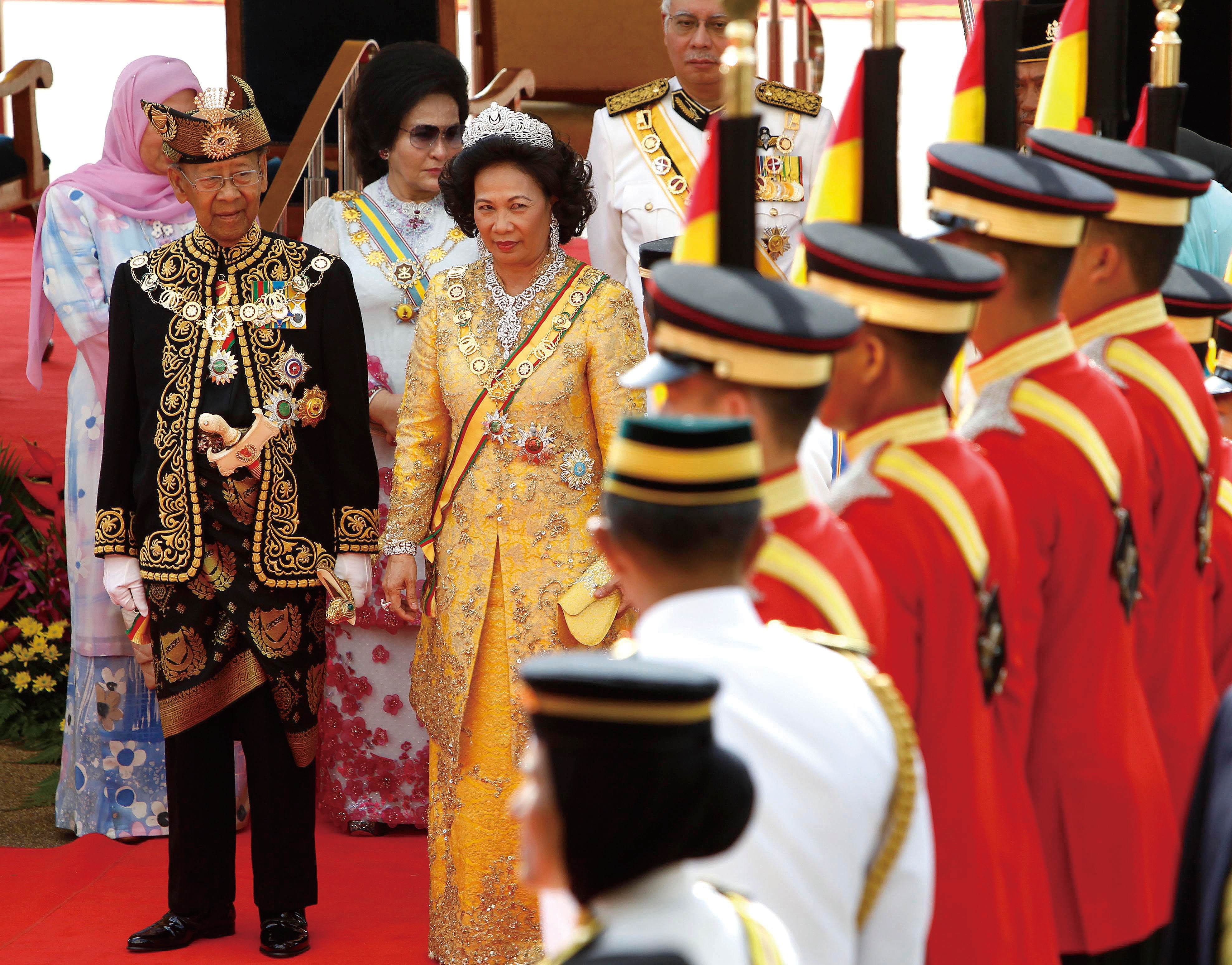 Malaysia's new King Sultan Abdul Halim, front left, Queen Haminah stand on the red carpet during a welcoming ceremony at the Parliament Square in Kual...