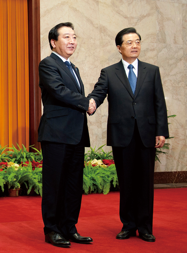 Japanese Prime Minister Yoshihiko Noda, left, shakes hands with Chinese President Hu Jintao prior to a meeting at the Great Hall of the People in Beij...