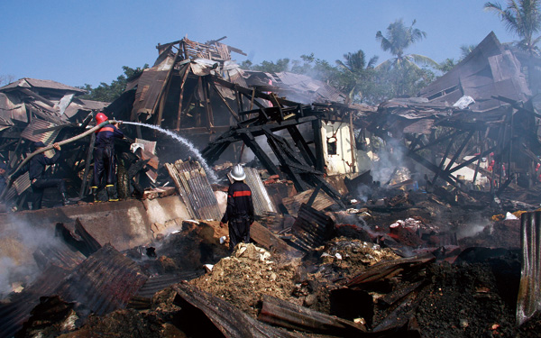 Myanmar fire fighters work amongst the destroyed buildings in Mingalar Taung Nyunt township in Yangon, Myanmar Thursday, Dec. 29, 2011. (Associated Pr...