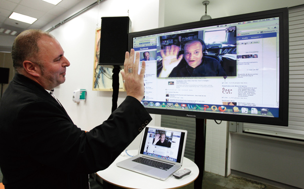 In this July 6, 2011 file photo, Facebook workers Mike Barnes, left, Video Chats with Jonathan Rosenberg, right, on Facebook during an announcement at...