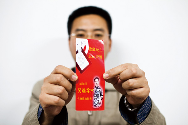 Qiao Mu, a professor at the Beijing Foreign Studies University, with one of the bookmarks he distributed to promote his campaign in Beijing, on Nov. 1...