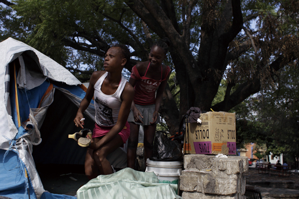 In this Jan. 3, 2012 photo, a young woman packs her belongings as she watches officials approach at a camp for people displaced by the 2010 earthquake...