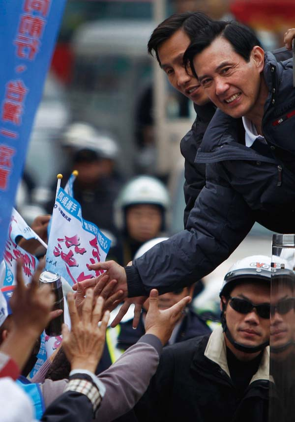 Taiwan's President and presidential candidate Ma Ying-jeou shares a high-five with a supporter as he tours neighborhoods Saturday, Jan. 7, 2012 in the...