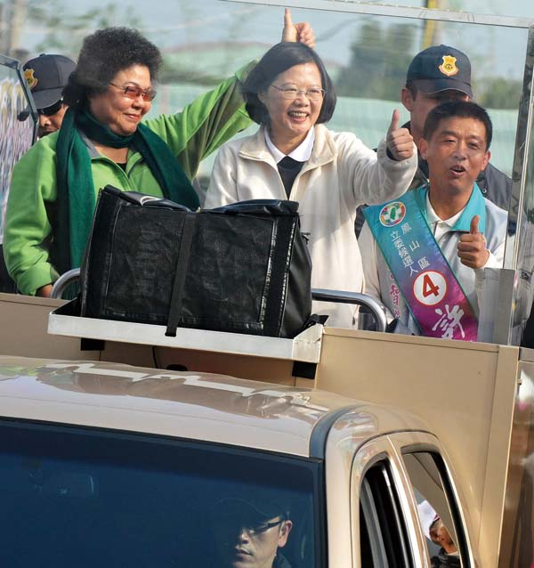 Taiwan's opposition presidential candidate Tsai Ing-wen (C) and Kaohsiung mayor Chen Chu (L) wave to supporters from an open-top jeep as they campaign...