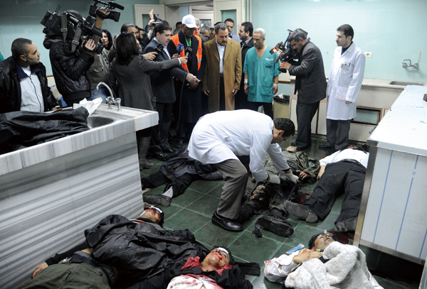 In this photo released by the Syrian official news agency SANA, an Arab league observer with the orange jacket, center, looks toward Syrian dead bodie...