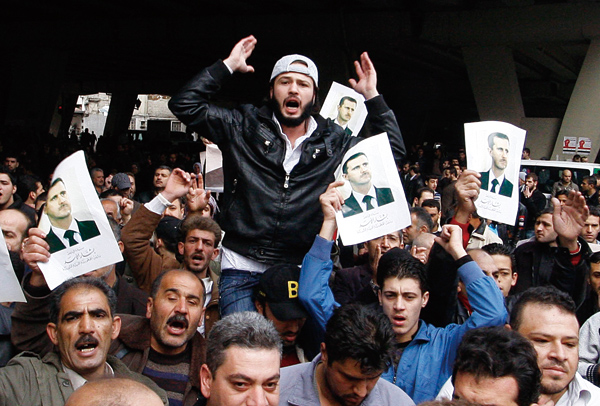 Pro-Syrian regime protesters, hold up portraits of Syrian President Bashar Asad and shout slogans at the scene bomb in Midan neighborhood, in Damascus...
