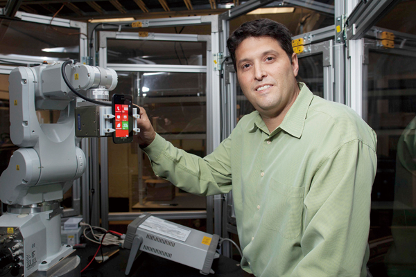 Terry Myerson, Microsoft's vice president for phone engineering, with a robot in a phone-testing lab at the company's offices in Redmond, Wash., Nov. ...