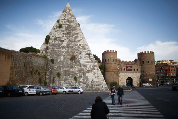 The Piramide, which was once a tomb but is now a metro stop, and the Porta San Paolo, a fortified gateway to the old city of Ostia Antica, near Rome, ...