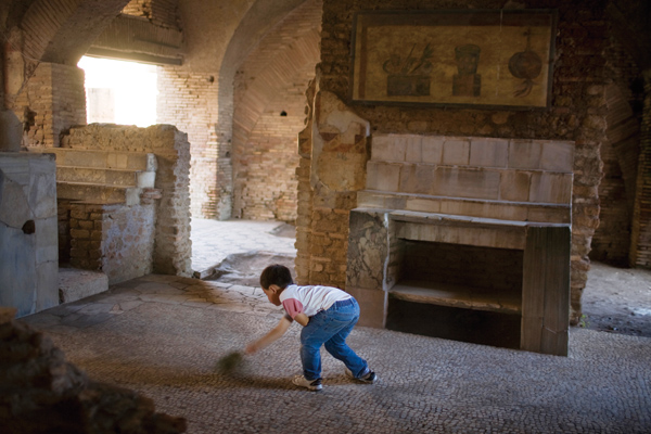 A child sweeps the floor of an old thermopolium, or restaurant, with a tree branch beneath a preserved painting in Ostia Antica near Rome, Oct. 30, 20...