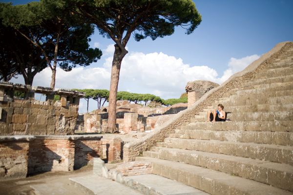 A visitor sits on the steps of an amphitheater in Ostia Antica near Rome, Oct. 30, 2011. (The New York Times)