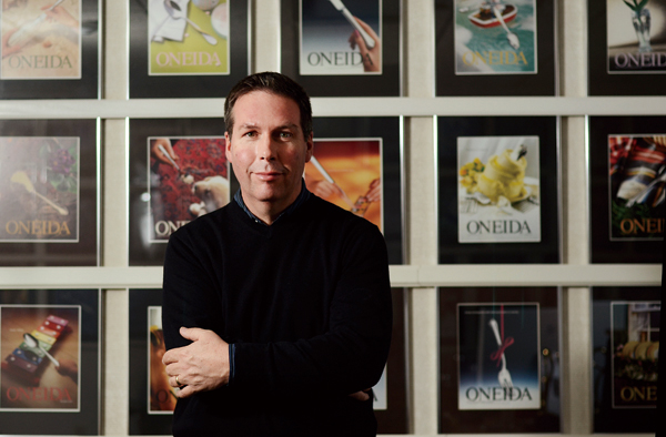 Paul Gebhardt, senior vice president of design for Oneida, near a wall of national advertisements for the company at his office in Oneida, N.Y., Dec. ...