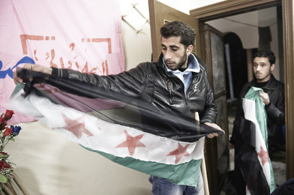 Syrian activists paint old Syrian flags to be used in a demonstration at a workshop on March 1, 2012 in Qusayr. (Agence France-Presse)