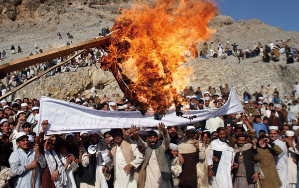 In this Feb. 24, 2012 file photo, Afghans burn an effigy representing U.S. President Barack Obama during an anti-U.S. protest in Ghani Khail, east of ...