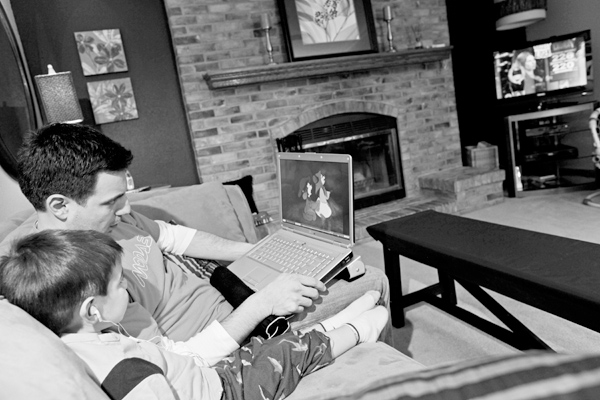 Steve Glynn and his son Max, 2, watch a movie on a laptop while the television is on at their home in Franklin, Wis., March 17, 2009. (The New York Ti...
