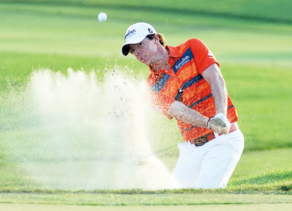 Rory McIlroy, of Northern Ireland, hits out of the sand on the 18th hole during the third round of the Honda Classic golf tournament in Palm Beach Gar...