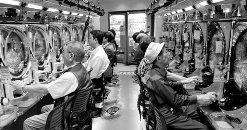日本民眾在東京的店內玩老虎機。