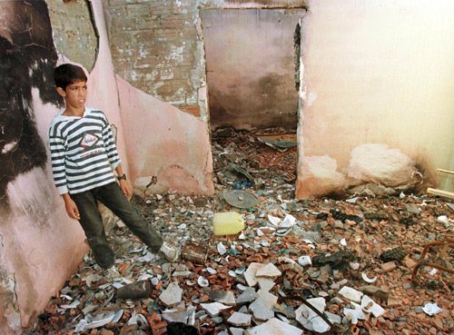 A child stands in the remains of his house that was destroyed in a guerrilla attack in the city of Rais, near Algiers, in this 1997 file photo.