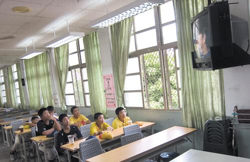 Members of Chongsywe Elementary School's baseball team watch their hero, New York Yankees pitcher Wang Chien-ming against the Seattle Mariners in thei...