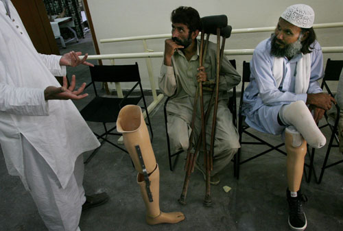 A Pakistani orthopedic doctor shows a custom built artificial leg to Abdul Hameed, center, at the Helping Hand clinic in Muzaffarabad in the Kashmir r...