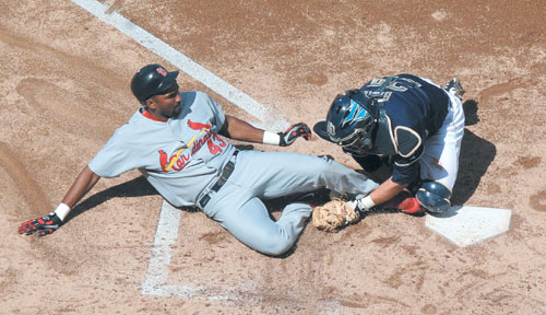 The St. Louis Cardinals' Juan Encarnacion is tagged out at home plate by San Diego Padres catcher Josh Bard to end the second inning during Game 2 of ...