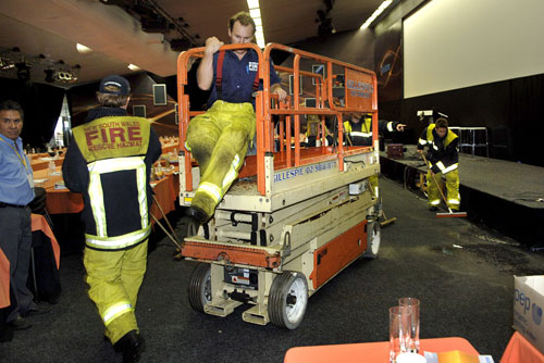Firemen examine and clean up the auditorium where Telstra Corp.'s investors meeting was interrupted by the sprinkler system being activated in Sydney ...