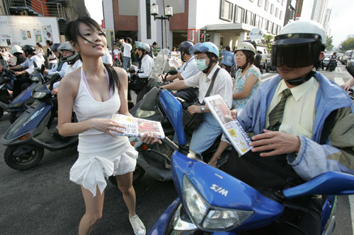 A young model aggressively distributes copies of the new Sharp Daily newspapers outside of a Taipei's subway station yesterday.