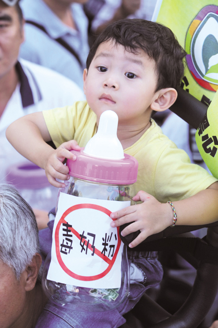 A toddler holds a fake feeding bottle, which bears a slogan attacking tainted Chinese dairy products at yesterday's rally.