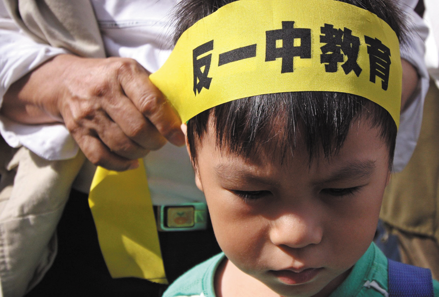 An elderly family member tries to fasten a sign saying 'Anti-one China education' on a young boy's head.
