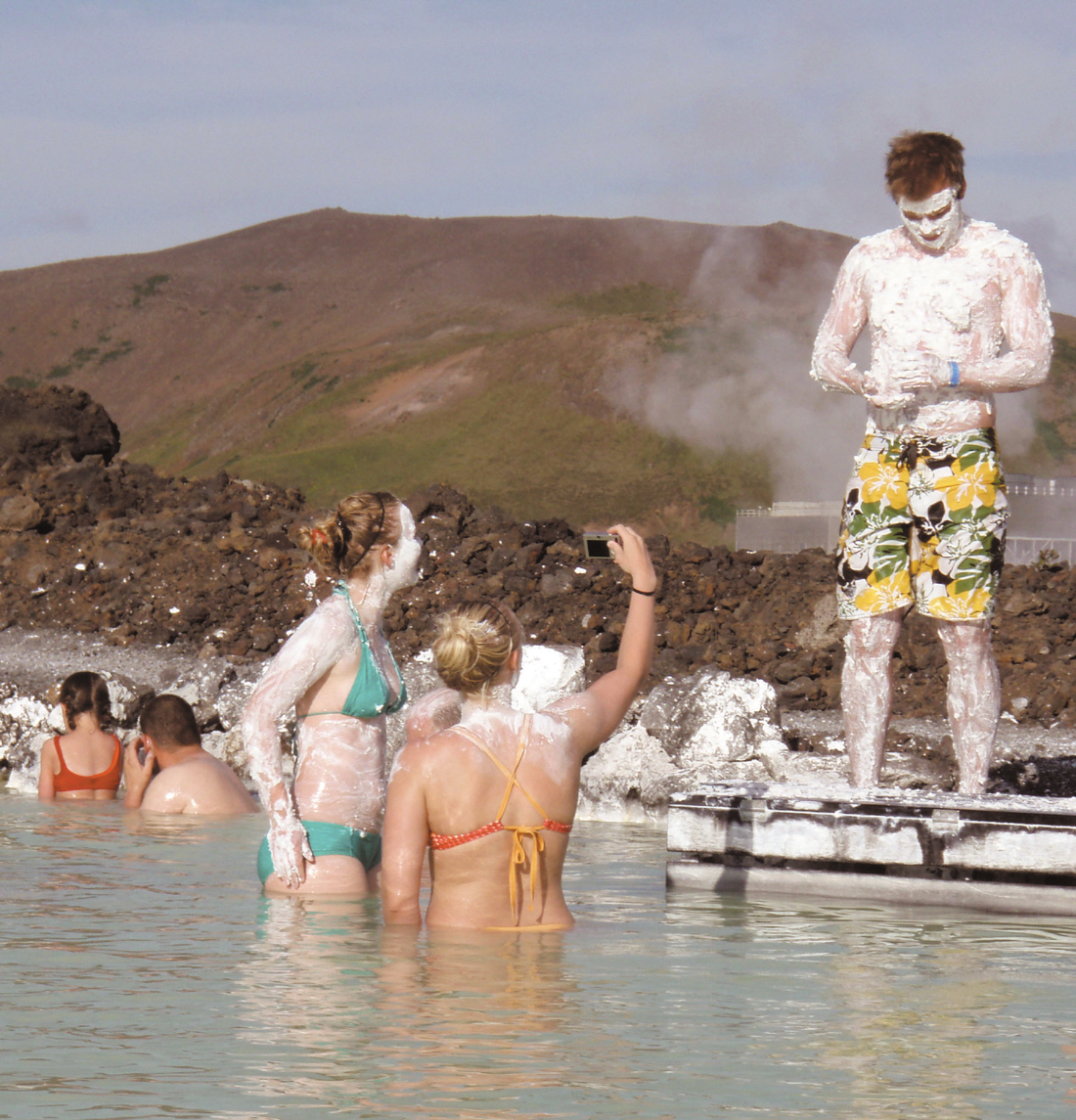 Visitors take in a mud bath and a photo at the Blue Lagoon in Iceland.