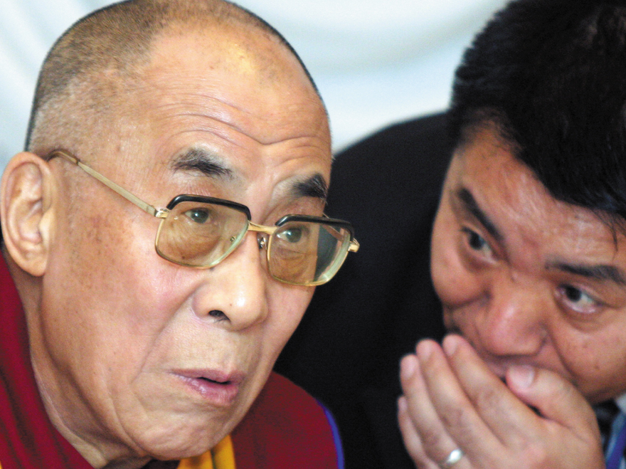 The Dalai Lama, the spiritual leader of Tibet, listens to his staff during a news conference in Narita city, Chiba prefecture, Japan in this April 200