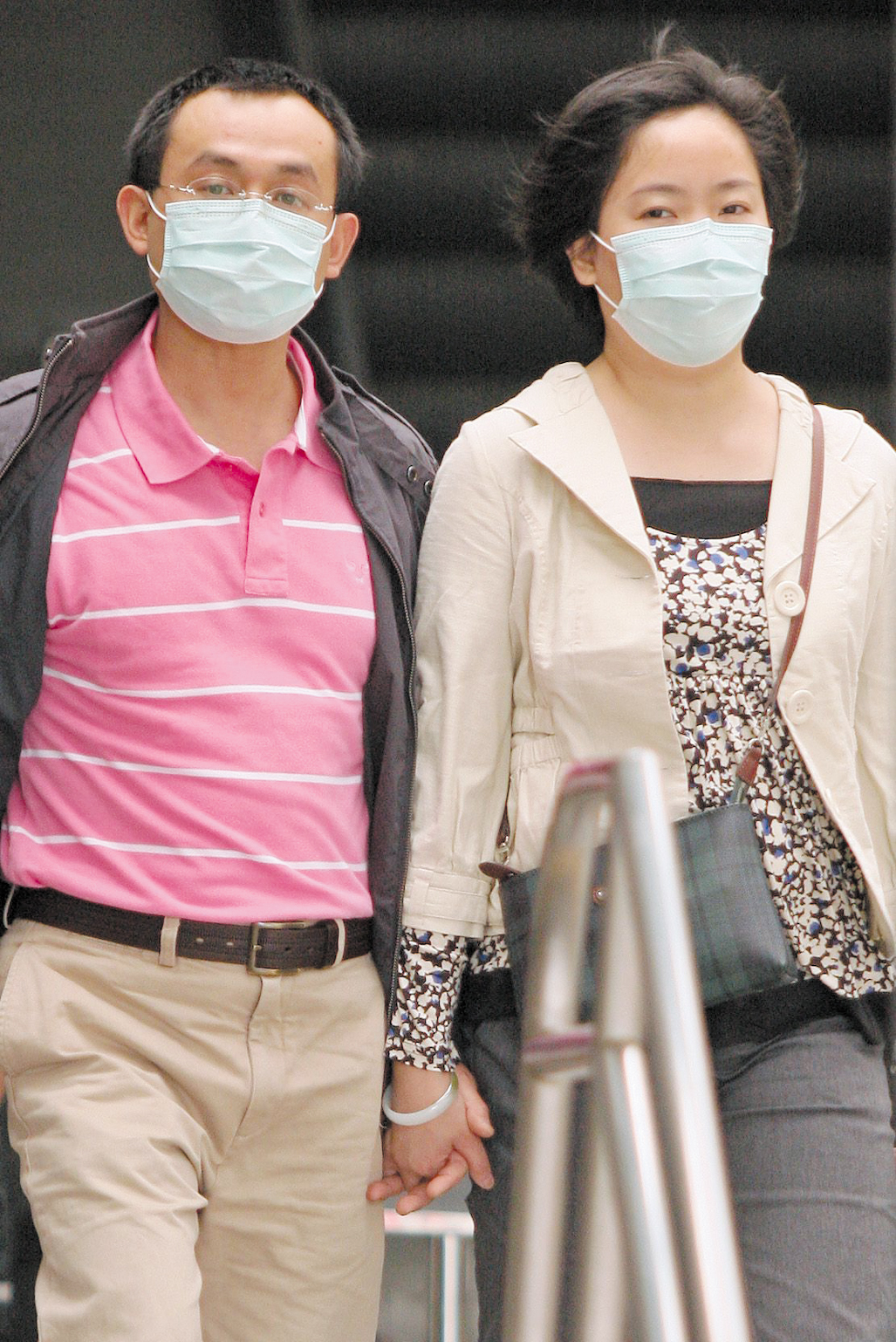 A couple walks in a MRT station yesterday with masks on their faces. Department of Health Minister Yeh Chin-chuan said the government is releasing 2 m...