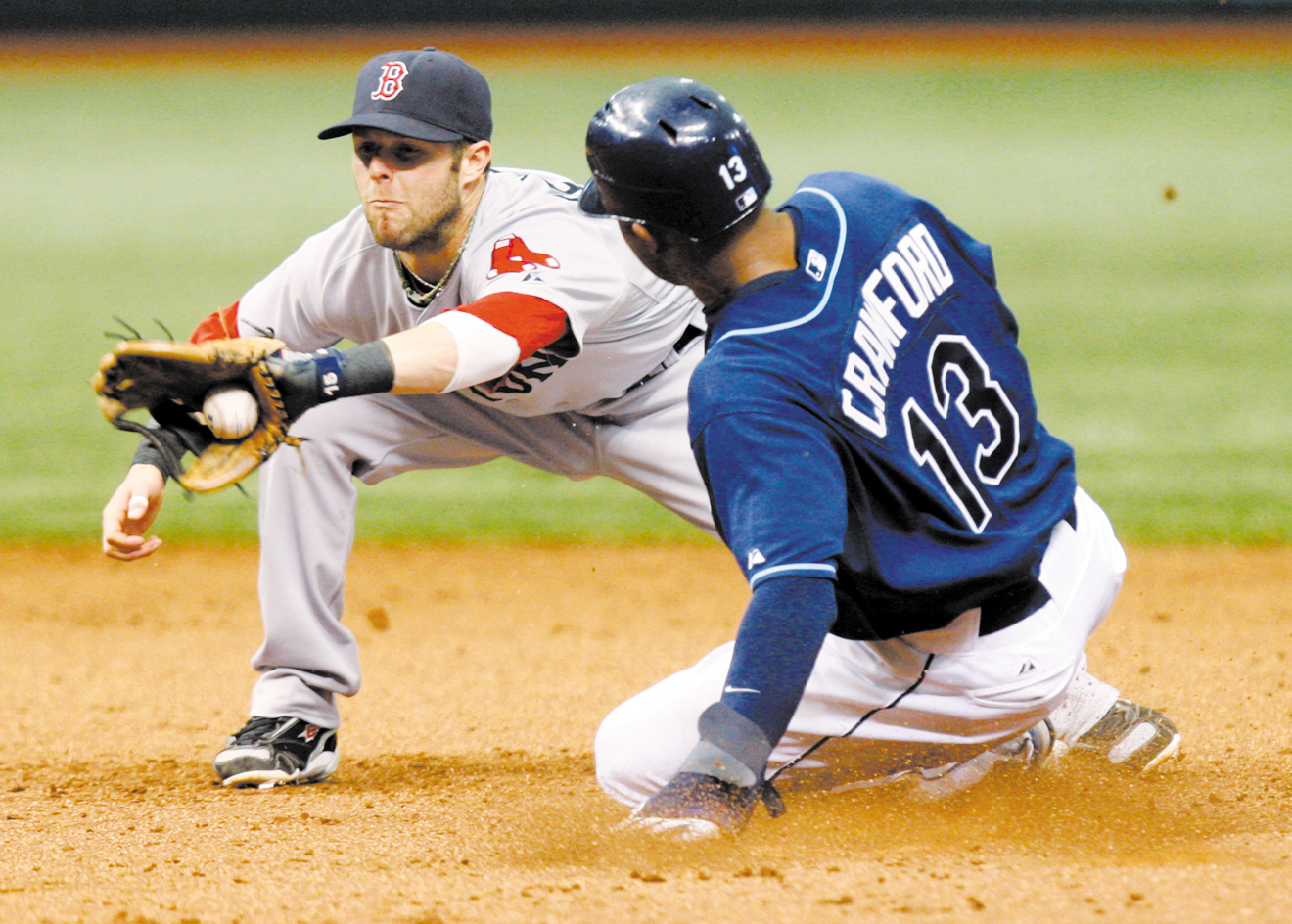 Tampa Bay Rays' Carl Crawford (13) slides in safely ahead of a tag by Boston Red Sox second baseman Dustin Pedroia in the eighth inning with his sixth...