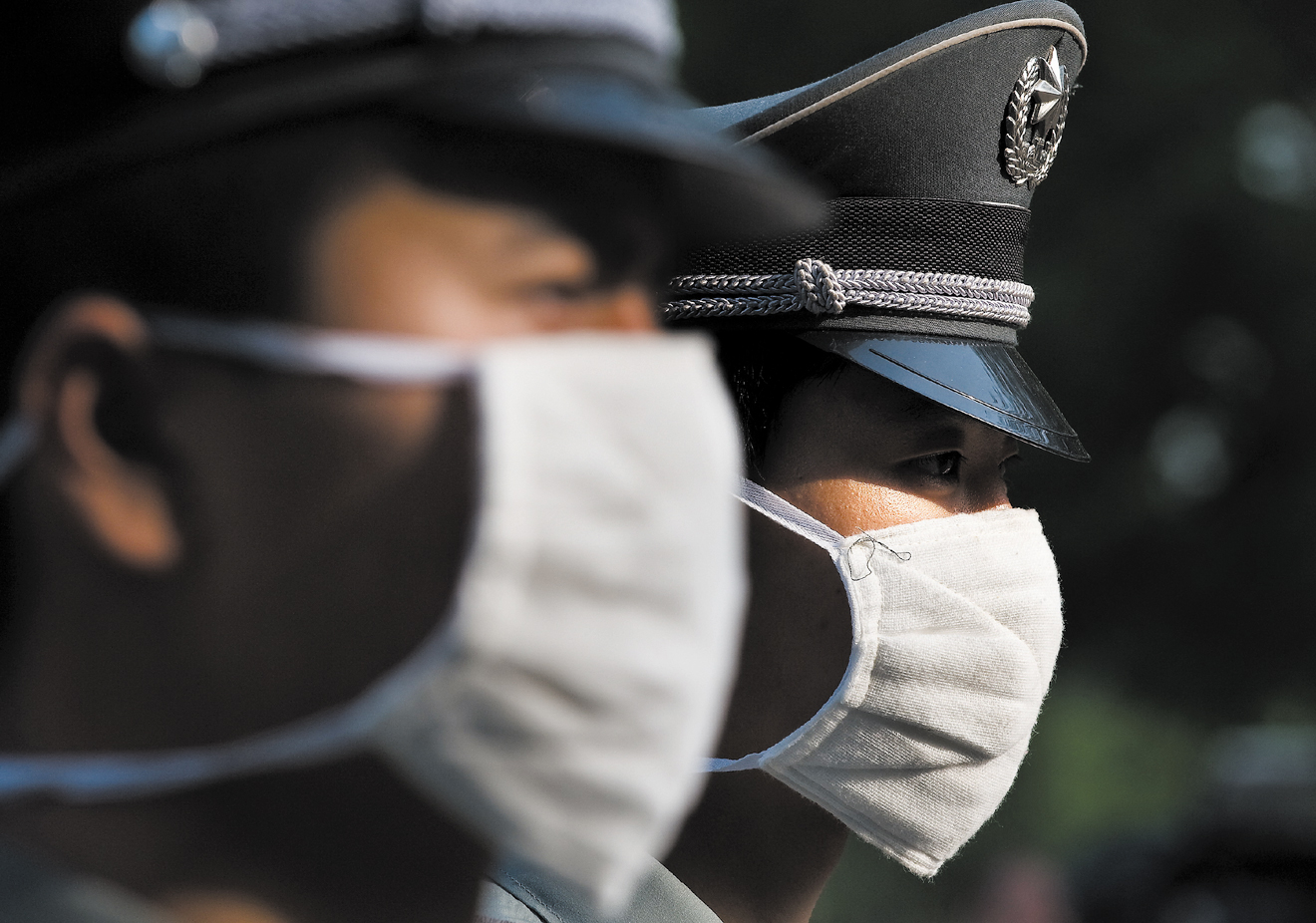 Chinese security officers wearing masks as a precaution against the swine flu stand guard as a convoy of vehicles carrying eight Mexican travelers dep...