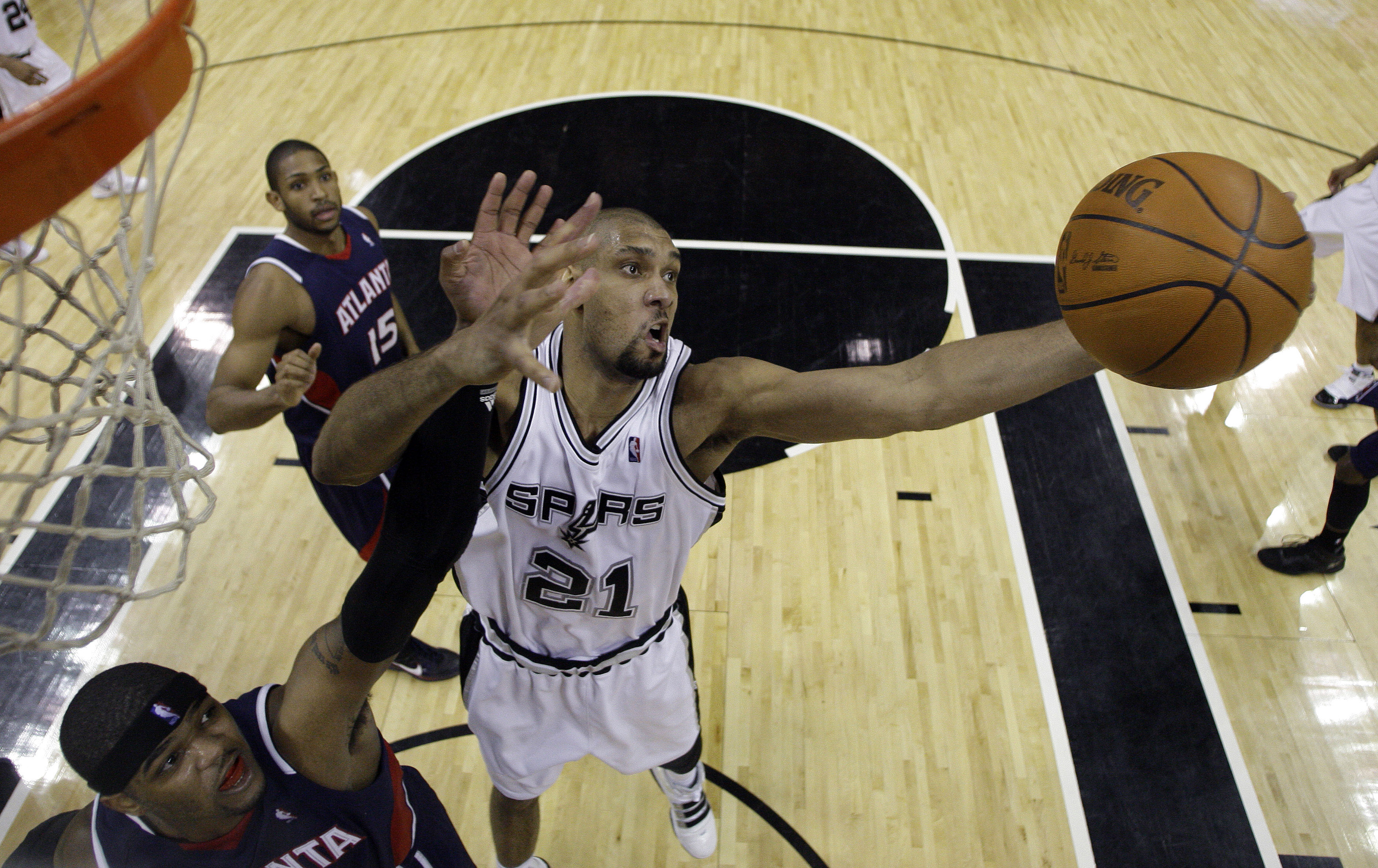 San Antonio Spurs' Tim Duncan (21) grabs a rebound over Atlanta Hawks' Josh Smith, left, as Hawks' Al Horford looks on during the fourth quarter of an...