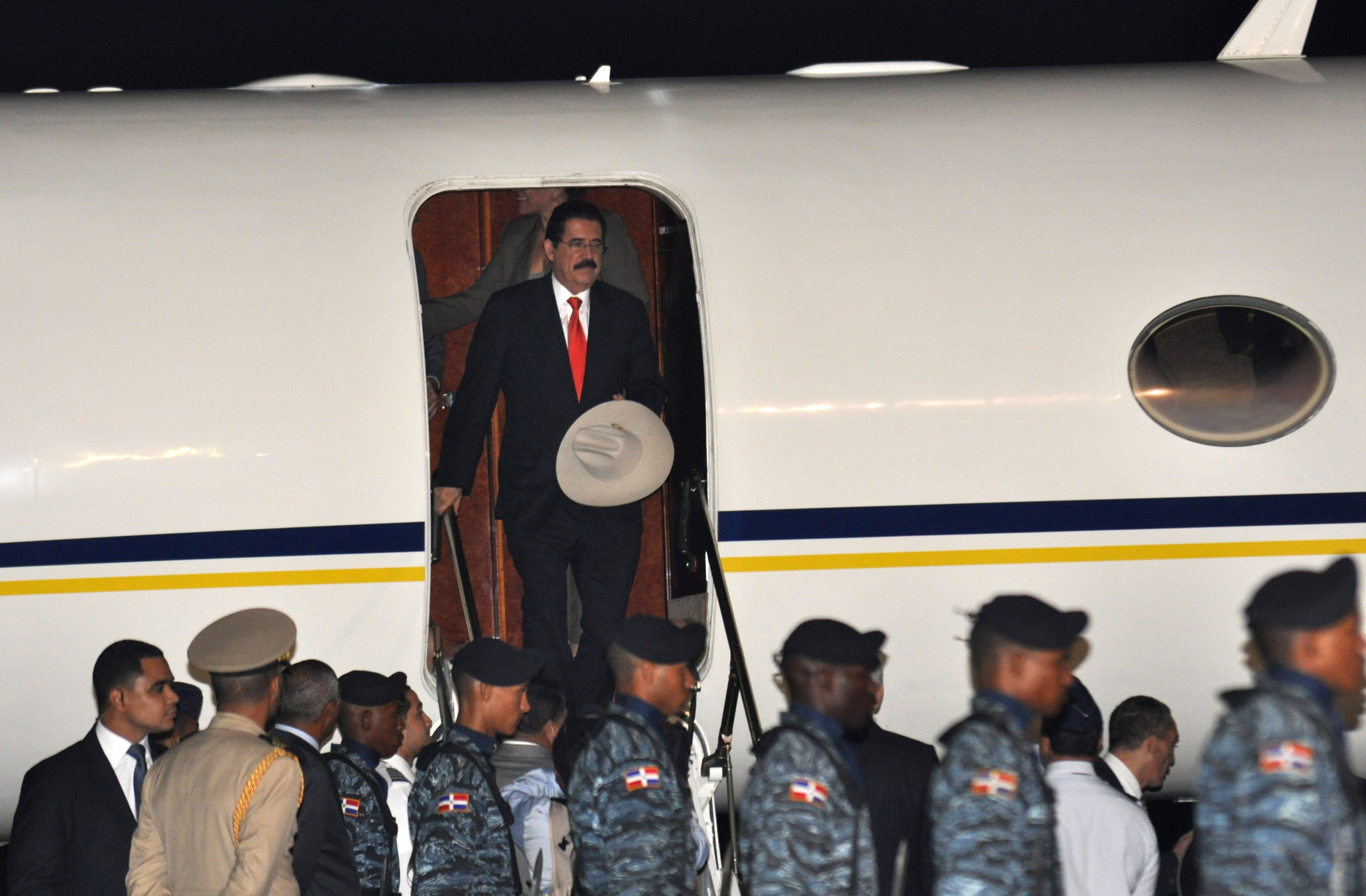 Honduras' ousted President Manuel Zelaya, top, exits an airplane as he arrives to the San Isidro air base on the outskirts of Santo Domingo, Dominican...