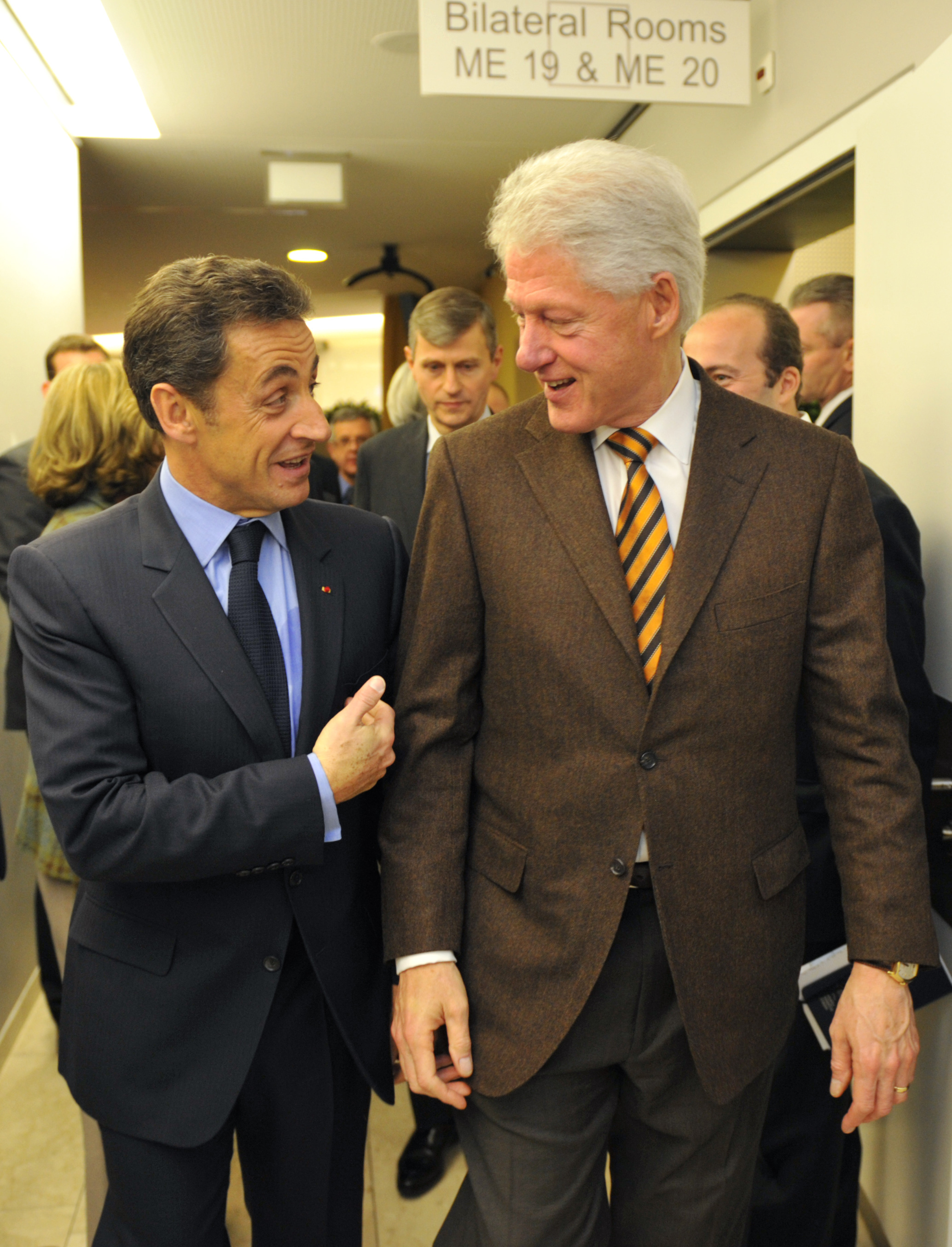 France's President Nicolas Sarkozy, left, walks with former U.S. President Bill Clinton, right, in the hallway of the main venue at the World Economic...