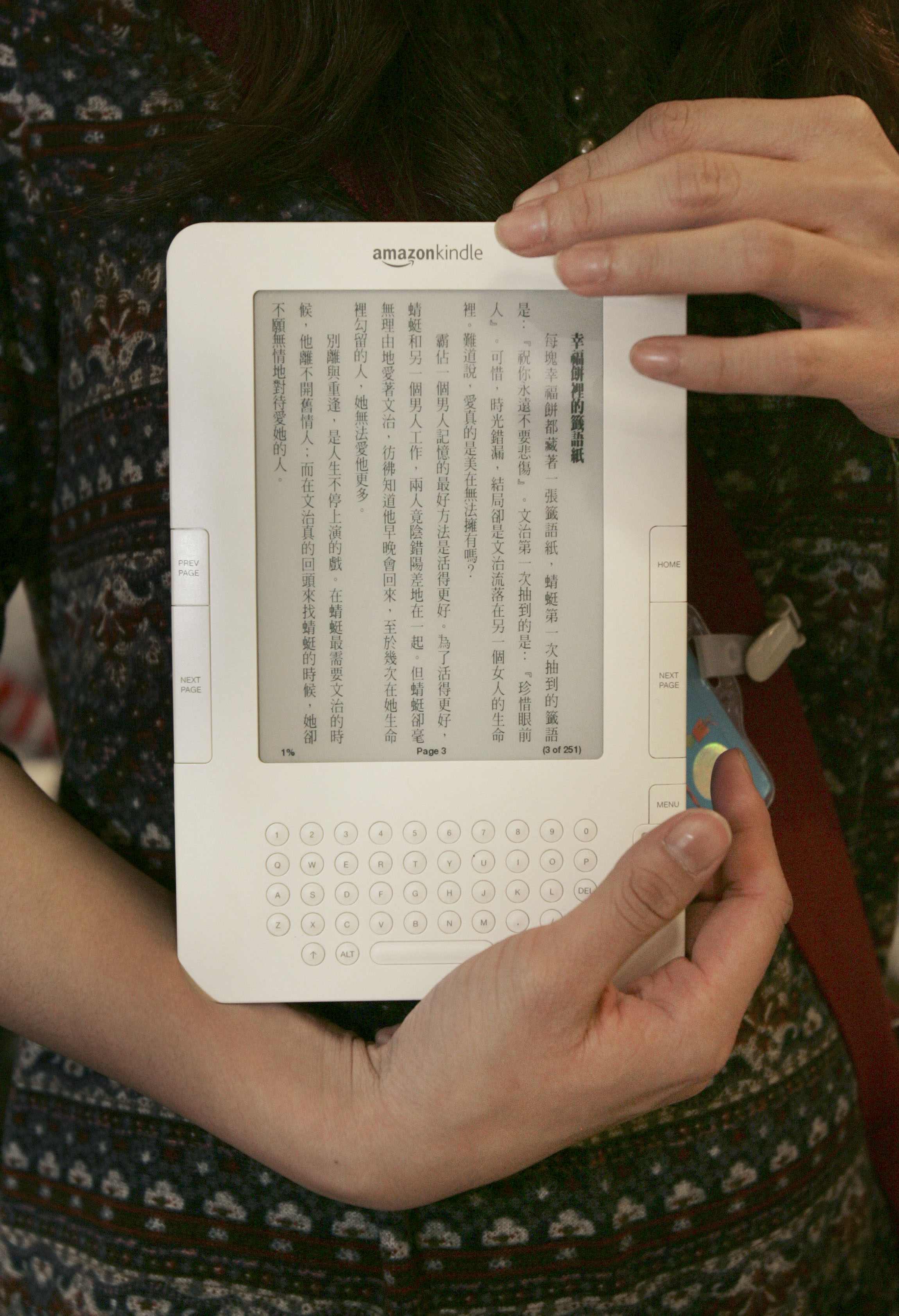 In this photo taken onWednesday, a booth attendant displays Chinese language content on an Amazon Kindle electronic book at the Taipei International B...